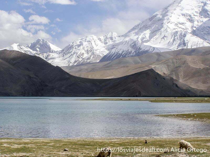 montañas con diferentes colores y al fondo nevadas con el lago karakul