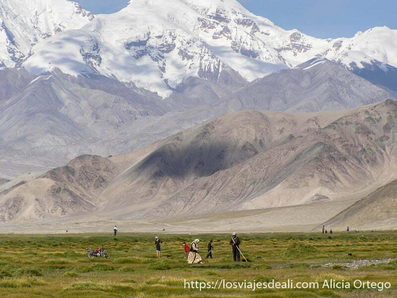 campesinos labrando tierra junto a las montañas del lago karakul
