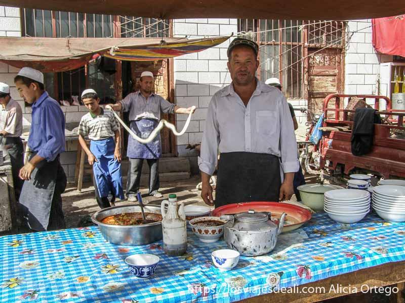puesto de comidas y al fondo haciendo fideos mercado de Kashgar