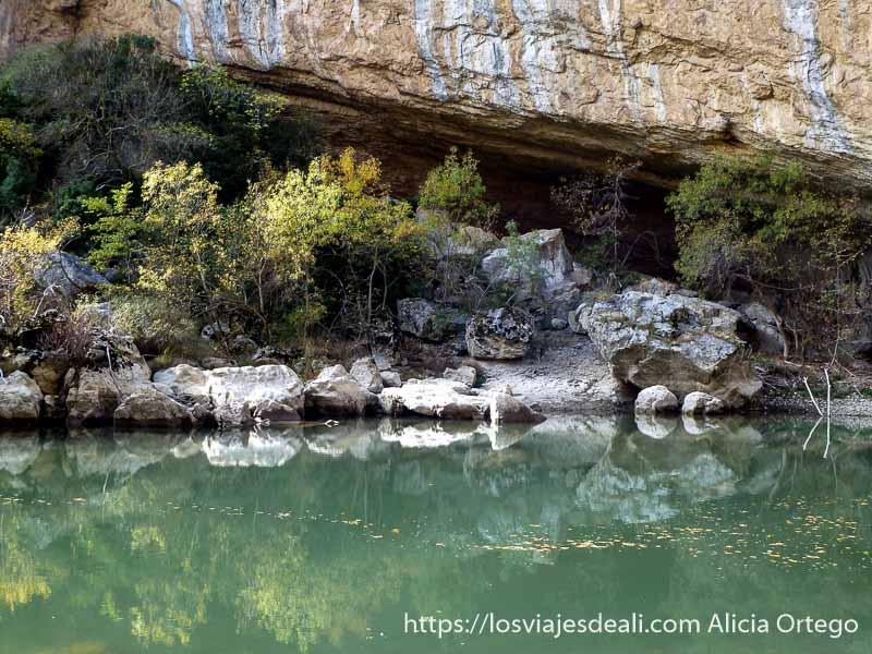 río de foz de lumbier con matorrales y rocas reflejándose en navarra