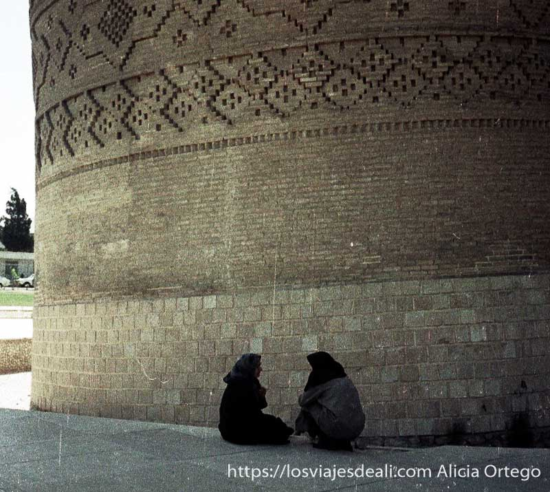 dos mujeres iraníes charlando en cuclillas junto a una torre histórica en shiraz