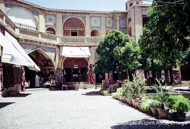patio de un caravanserai con tiendas de alfombras, fuente y árboles en el centro en shiraz