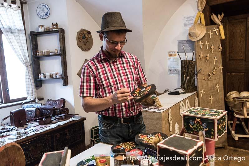 artesano pintando flores en objetos de madera en sighisoara
