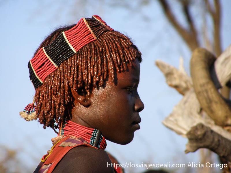 niña hamer con pelo de trencitas untado de ocre y diadema de bolitas rojas y negras tribu hamer