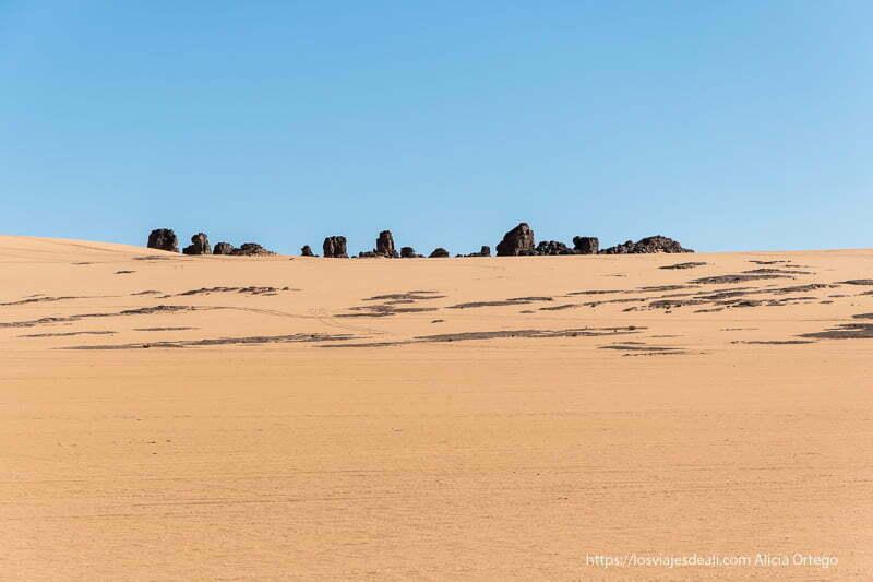 duna con fila de rocas en el horizonte viaje a Argelia