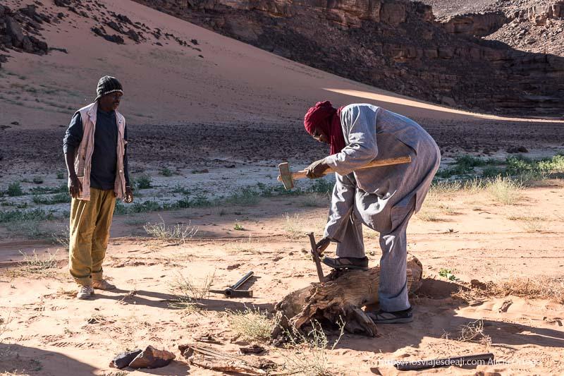 tuareg cortando un tronco de acacia en el desierto con gran martillo y escoplo