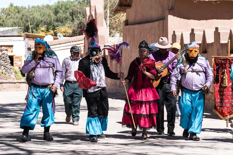procesión de hombres con máscaras y una chica vestida con corona San Pedro atacama