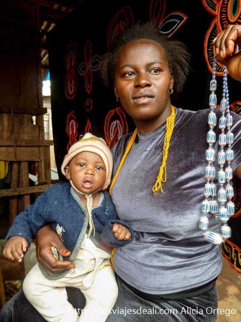 mujer de bamenda con bebé sosteniendo collar para vender