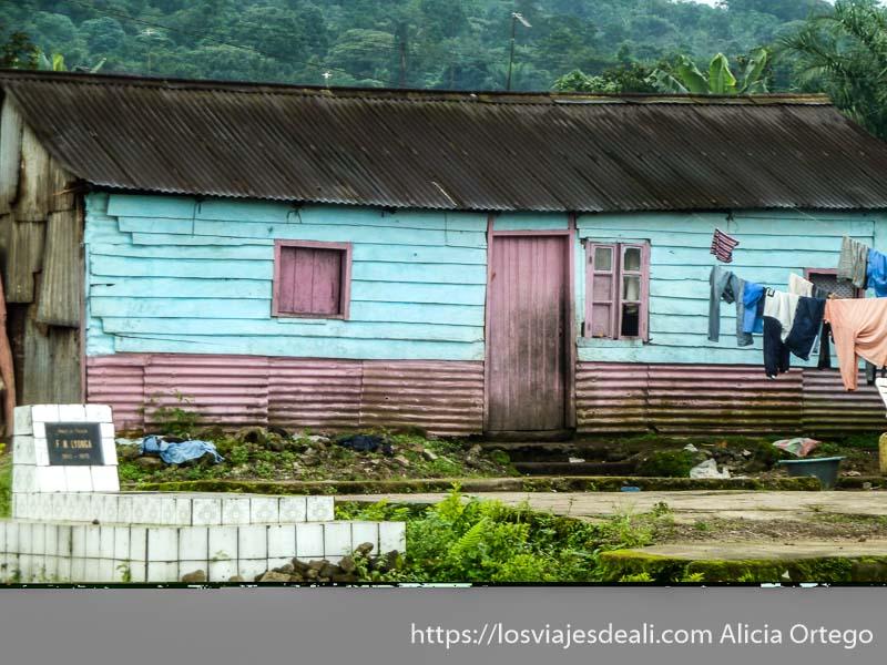 casa de madera pobre pero pintada de azul y rosa con tumba al lado en buea