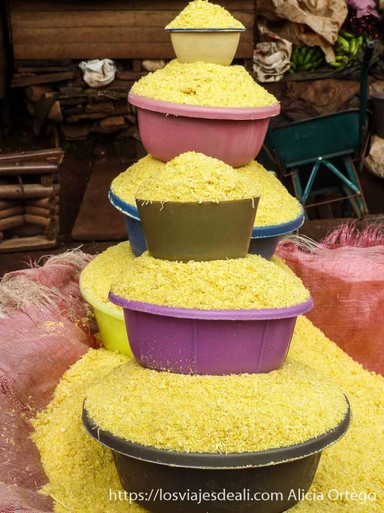barreños de colores llenos de maíz amarillo dispuestos en una artística pila en foumban