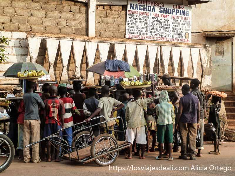 montón de niiños viendo la tele con sus mercancías en la cabeza, en la calle foumban