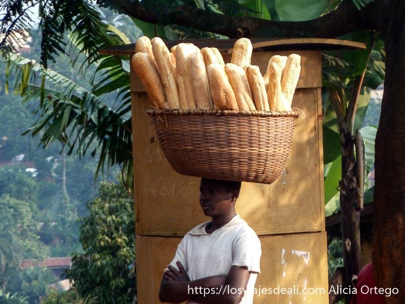 chico con gran cesta en la cabeza llena de barras de pan en foumban