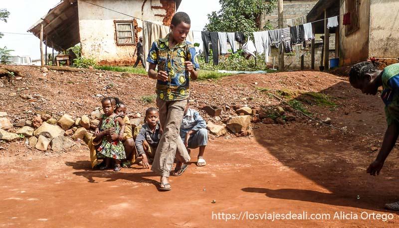 niños jugando a las canicas en tierra roja en foumban