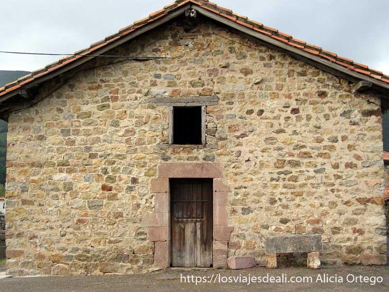 fachada de casa de piedra con banco junto a la puerta y tejado a dos aguas