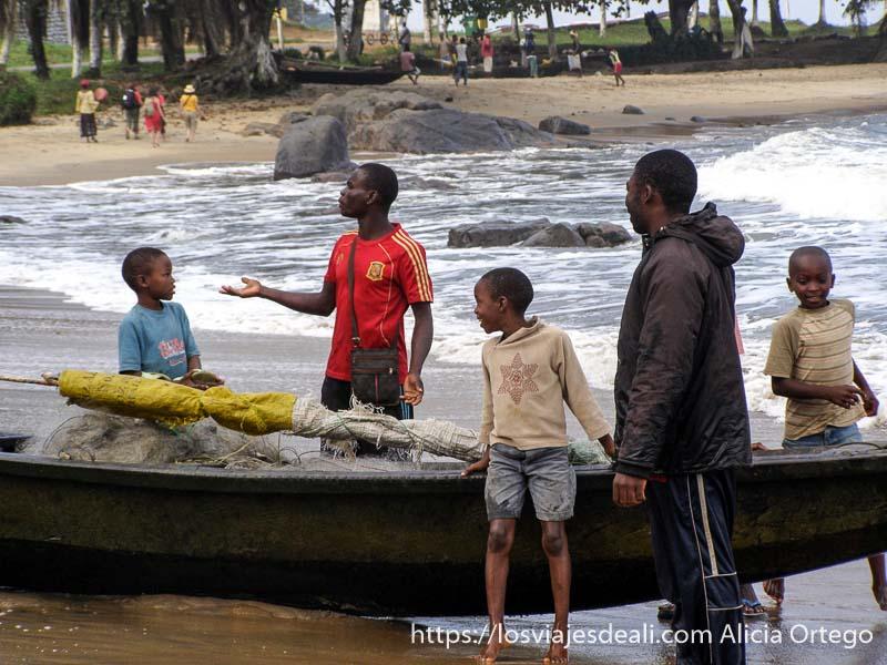 niños y mayores sacando barca del mar sur de camerún kribi