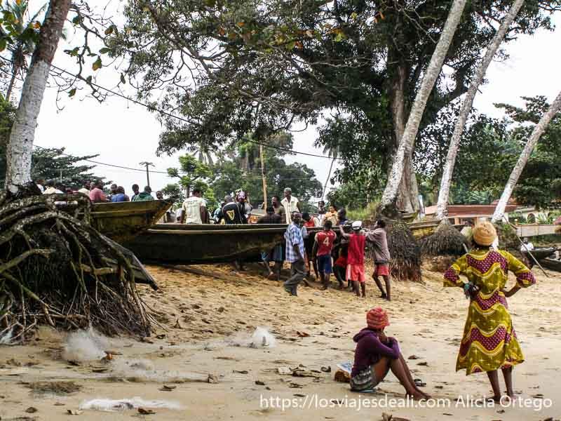 pescadores sacando las barcas del mar mientras dos chicas miran sur de camerún kribi