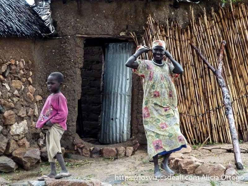 mujer sonriente y niño en la puerta de su casa trekking en los montes mandara de camerún