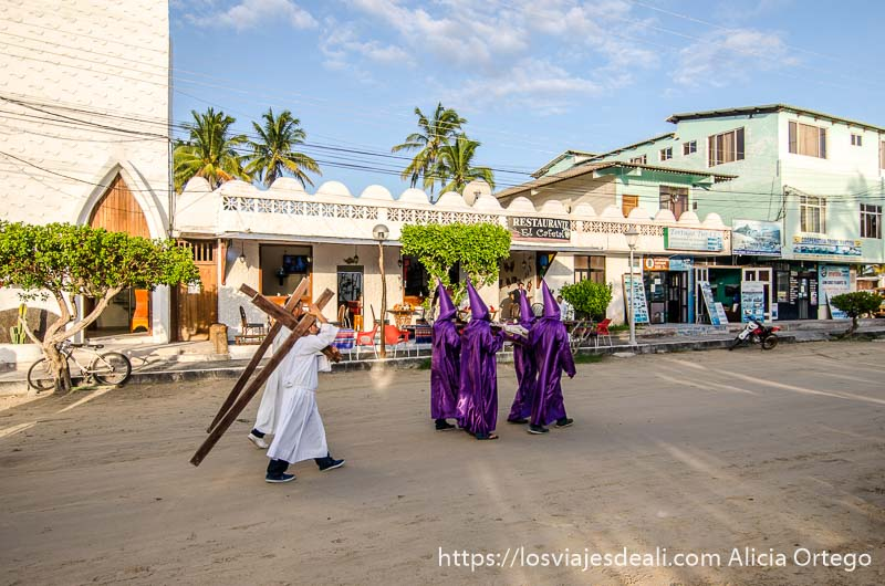 procesión de semana santa con cuatro encapuchados de morado y dos monaguillos llevando cruces en isla isabela galápagos