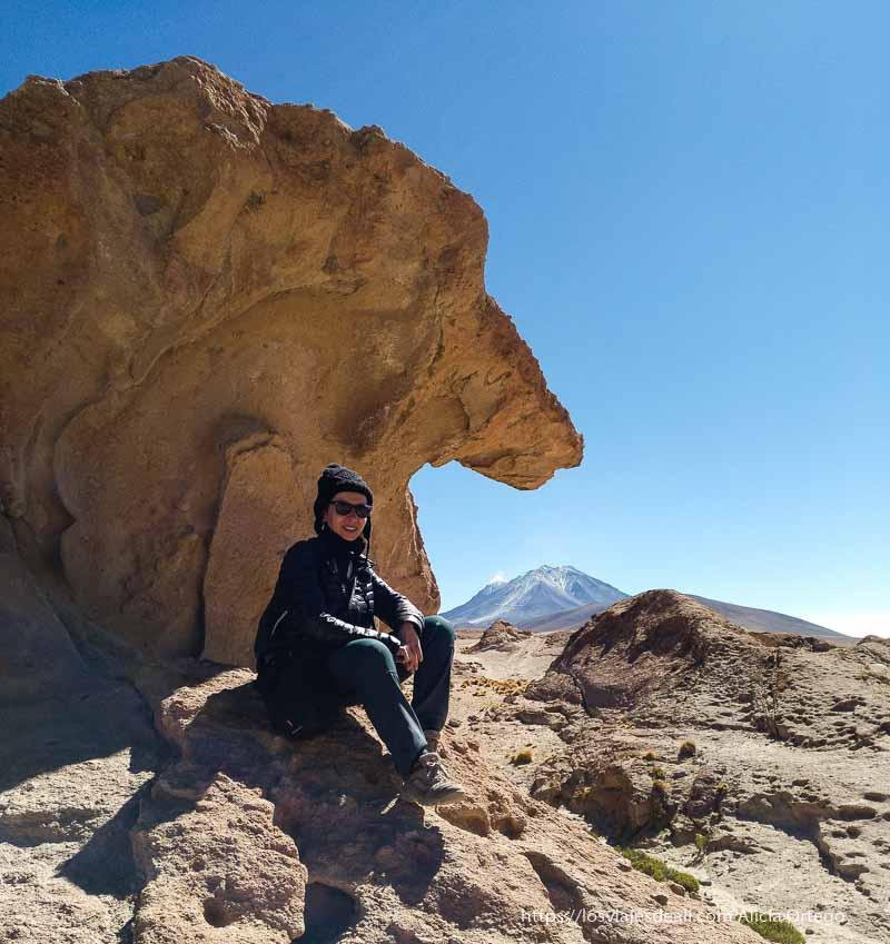 sentada bajo una roca con volcán collagua al fondo en la reserva nacional de fauna andina eduardo avaroa