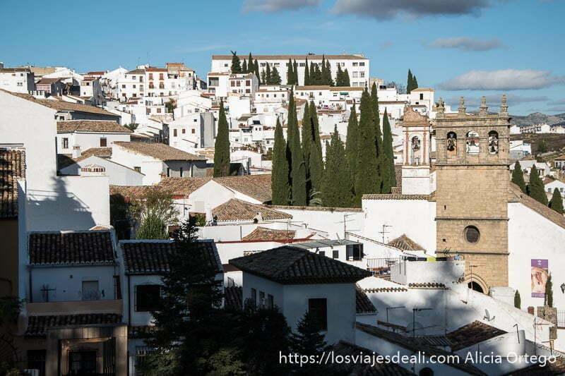 iglesia y casas blancas con cipreses sobresaliendo escapada a ronda