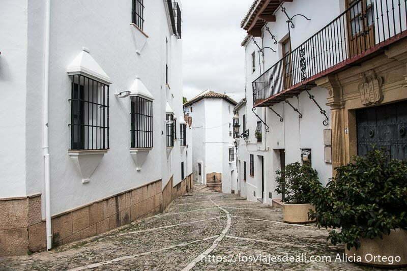 calle empedrada con casas blancas con balcones con rejas de hierro escapada a ronda