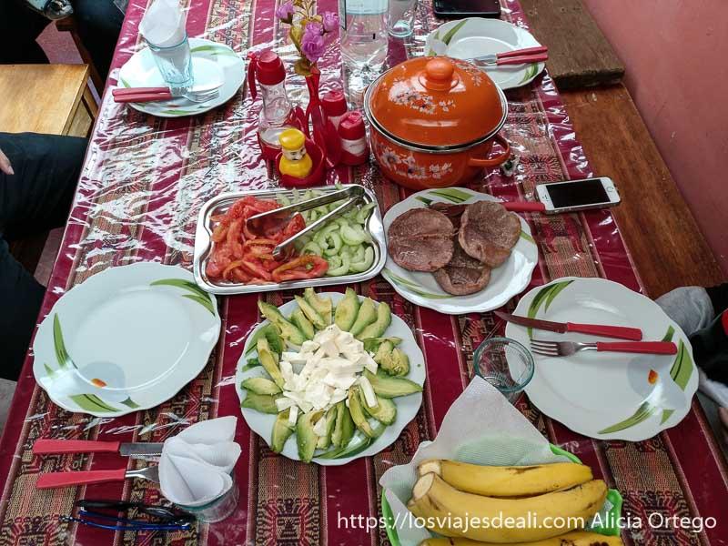 mesa puesta para comer con plato de filetes de llama y ensalada de ahuacate con queso fresco en bolivia