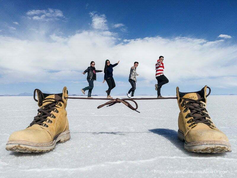 dos botas unidas por sus cordones y cuatro personas bailando sobre ellos foto con perspectiva en el salar de uyuni