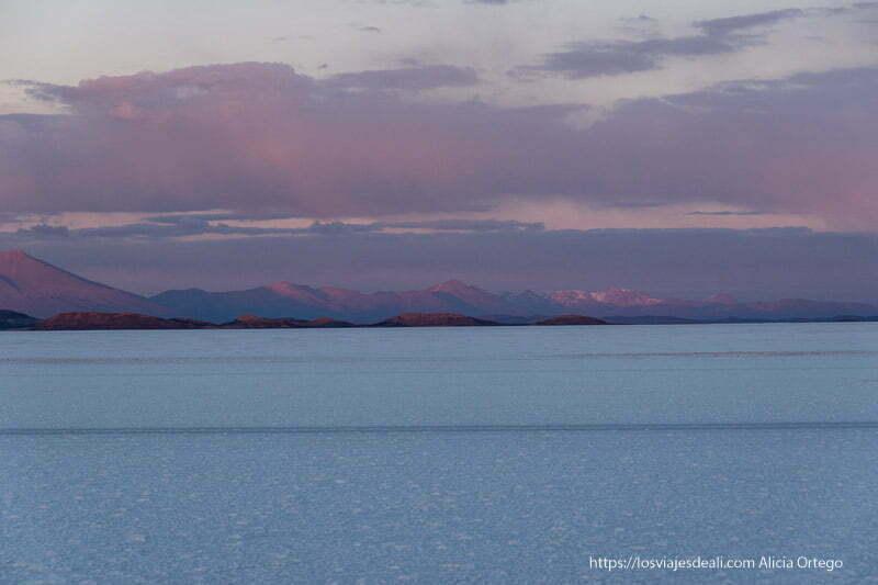 cordillera de los andes al fondo con nubes rosadas y planicie blanca