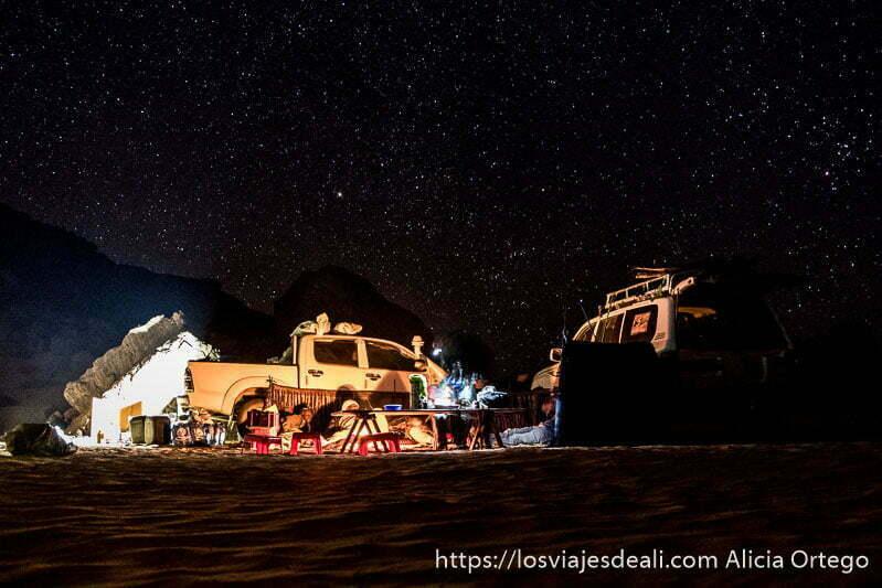 campamento en el desierto iluminado por el fuego con cielo lleno de estrellas consejos para viajar a argelia