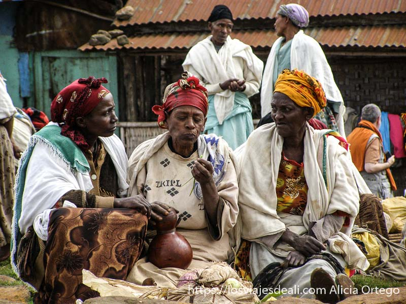 tres mujeres mayores con pañuelos de colores en la cabeza sentadas una de ellas con una calabaza de licor en la mano