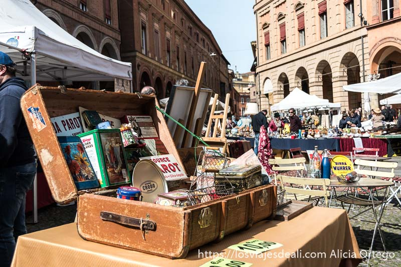 antiguo baúl con latas antiguas y otros cachivaches en el mercadillo de antigüedades en un día soleado