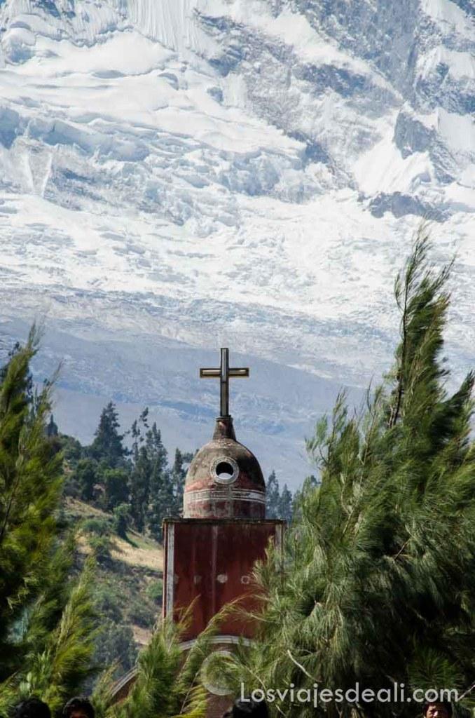 torre de iglesia con cúpula y cruz destacándose en la nieve de los andes