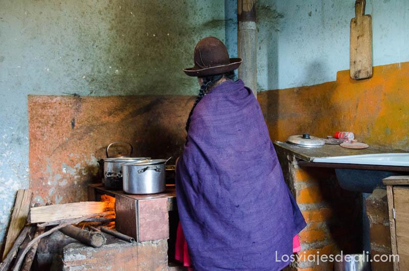 señora cocinando en horno de leña con manto de color morado y sombrero