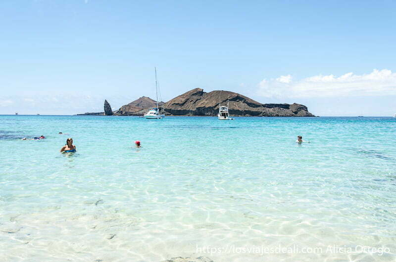 gente bañándose en el mar azul turquesa con islote volcánico al fondo y un barco
