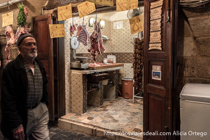 hombre pasando delante de carnicería con piezas colgando