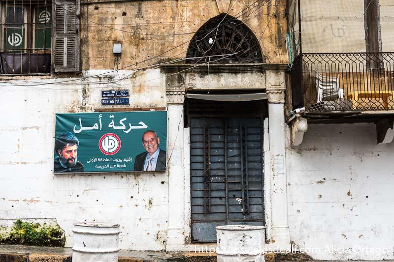 puerta de edificio antiguo y un cartel de partido chiíta en la pared