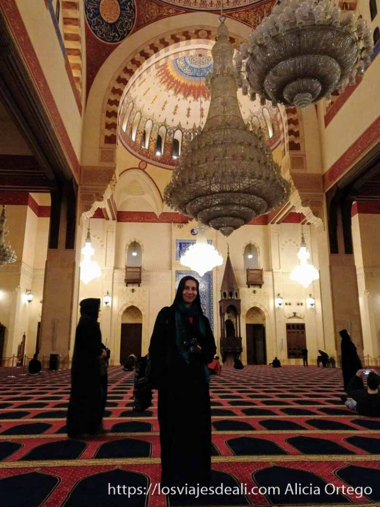 vestida con la abaya en la mezquita bajo dos lámparas enormes