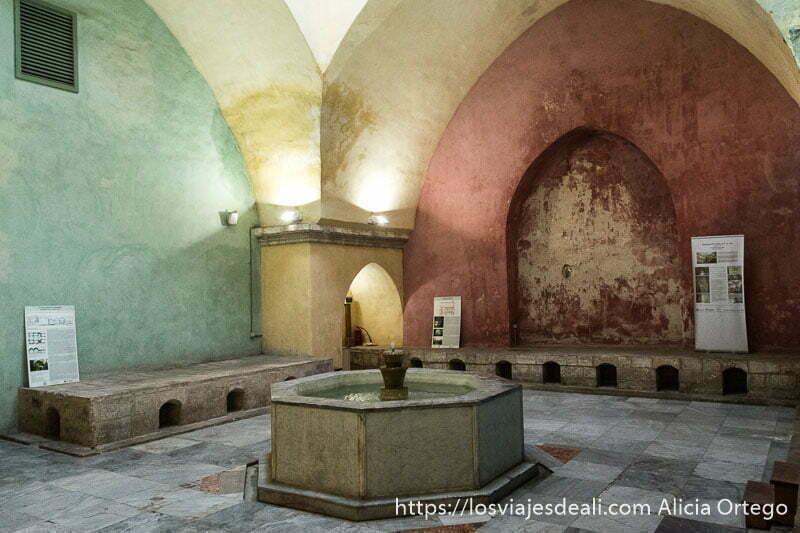 interior de hammam antiguo con arcos y paredes de color verde y rojo con fuente en el centro