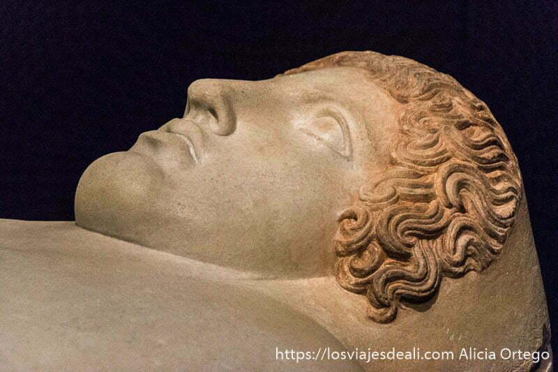 rostro humano hecho en mármol con cabello rizado y ojos mirando hacia arriba