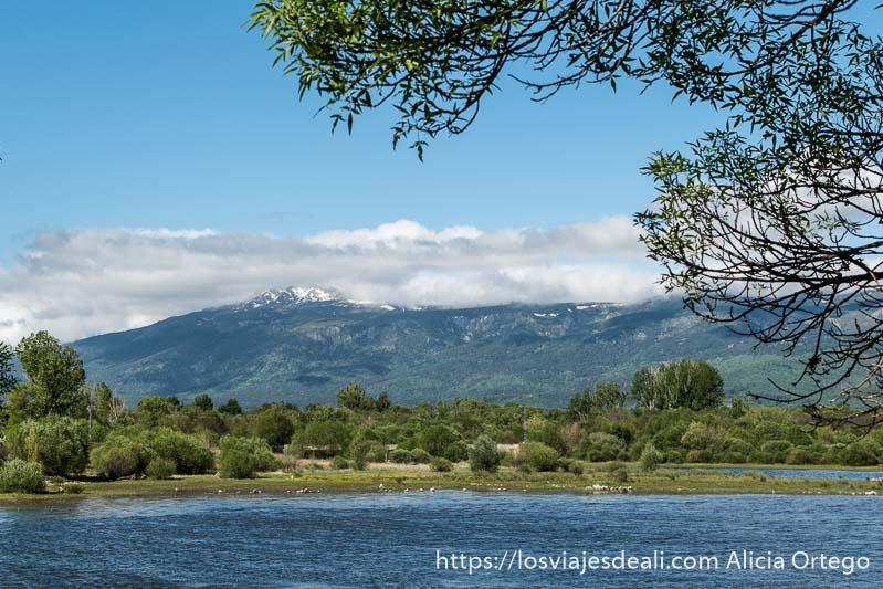 embalse de pinilla con montañas al fondo con algo de nieve en las cumbres
