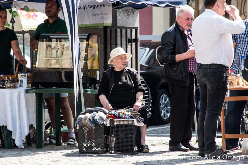 señora mayor vestida de negro con gorro blanco vendiendo calcetines