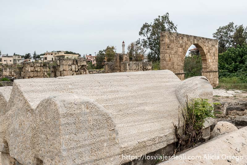 sarcófago de mármol blanco y arco detrás en las ruinas de tiro