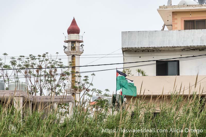 minarete de mezquita y banderas palestinas junto a una casa al lado de las ruinas de tiro