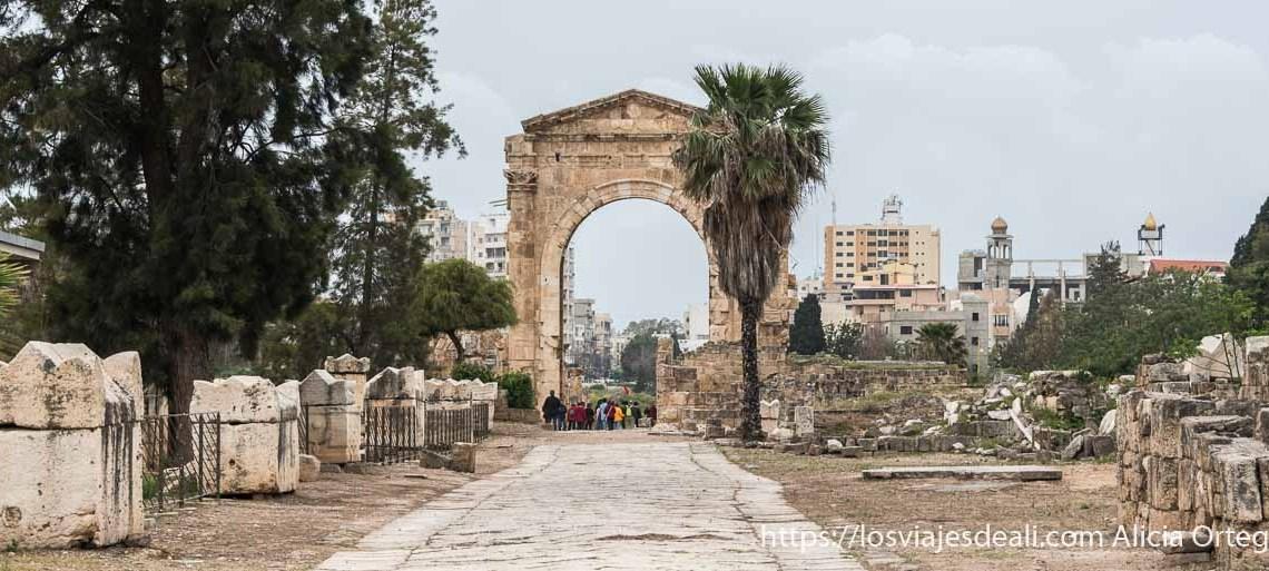arco de triunfo romano al fondo de calzada antigua y sarcófagos en línea a la izquierda