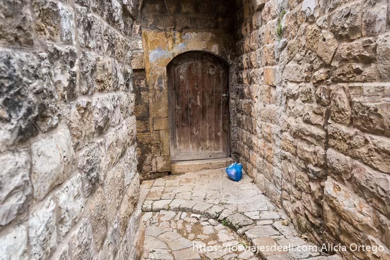 calle de suelo y paredes de piedra que hace curva con puerta de madera al fondo y una bolsa de basura de color azul junto a ella en el suelo