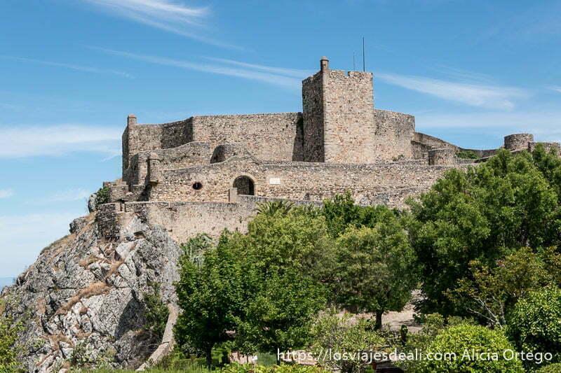 murallas del castillo de marvao con varios niveles sobre la roca y árboles debajo