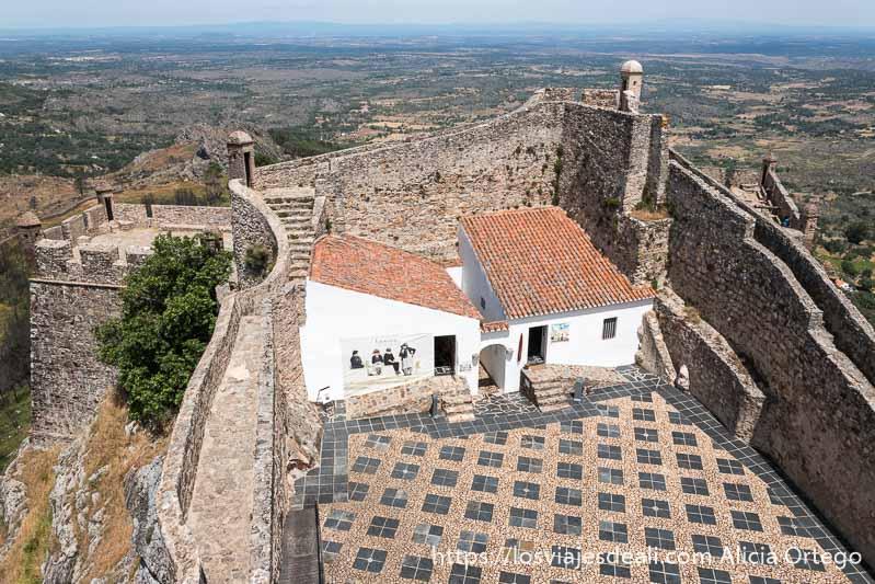 patio del castillo de marvao con murallas con escaleras y baluartes y dentro dos casas blancas con tejado rojo adosadas a las murallas