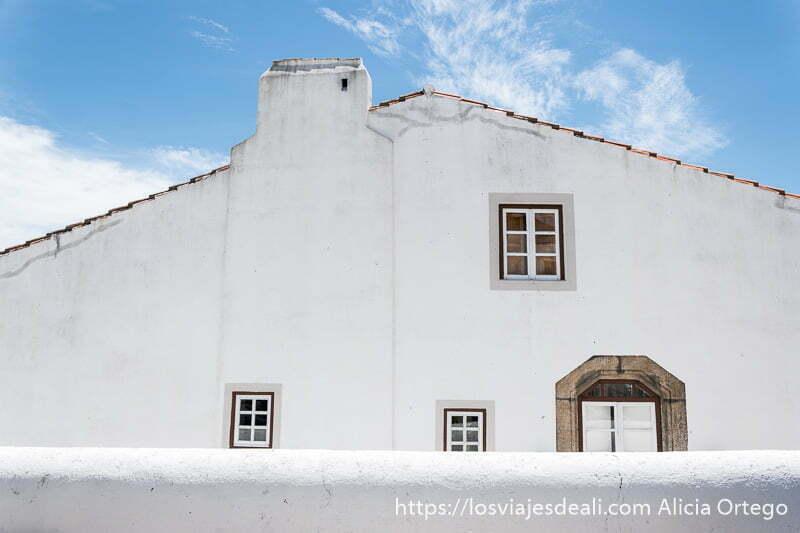 fachada de casa blanca con ventanas con cuarterones también blancos y cielo azul arriba en marvao