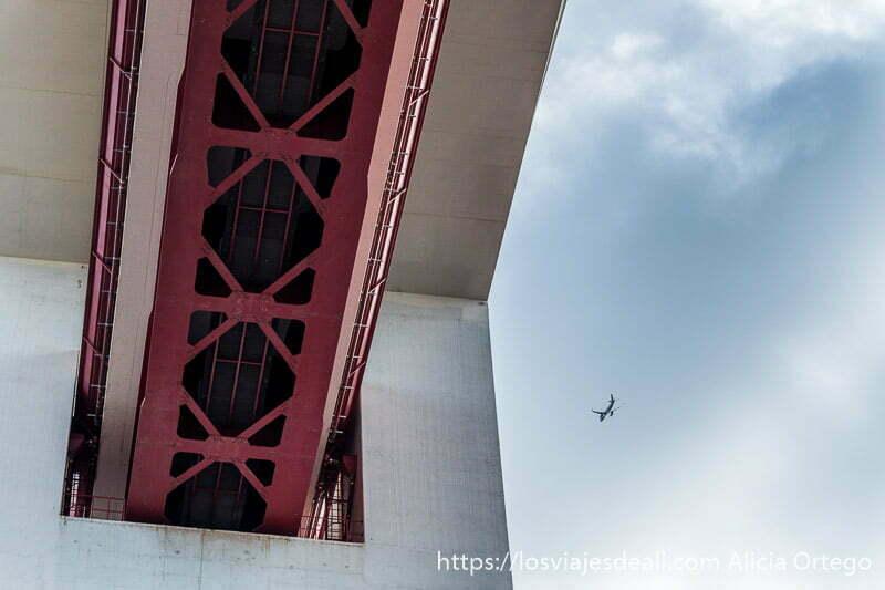 avión junto a estructura gigante del puente de lisboa en Belem