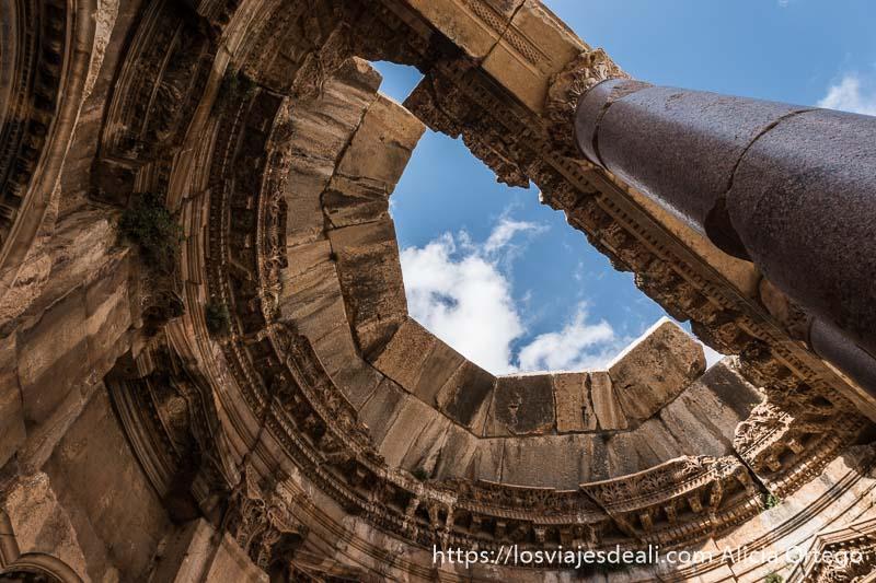 columna de granito rosa sosteniendo viga de piedra y parte del techo en forma de bóveda todo de piedra en las ruinas de baalbek